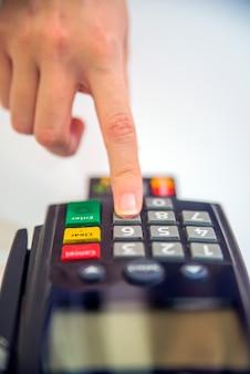 Pos端末でサービスを提供するカードのクローズアップ。 posとクレジットカードのカラー画像。白い背景にクレジットカードリーダーマシン