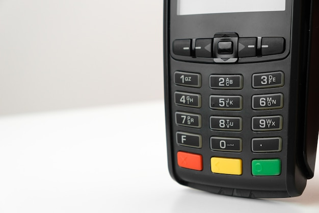 Pos terminal or credit card reader machine on the white table with copy space