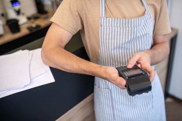 Pos-терминал для кафе. мужские руки держат черный удобный pos-терминал, выбирая нажатие кнопки на нем в кафе, без лица