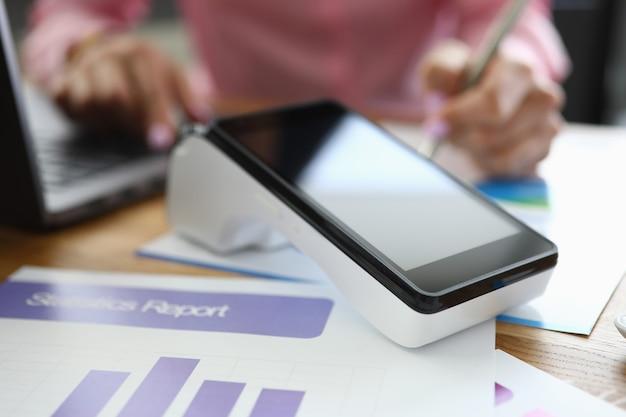 Pos-терминал для финансового отчета находится на столе. проведение банковских операций с использованием концепции pos-терминала.