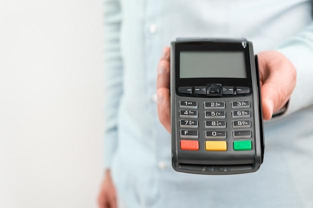 복사 공간이 있는 흰색 테이블의 Pos 터미널 또는 신용 카드 판독기 프리미엄 사진
