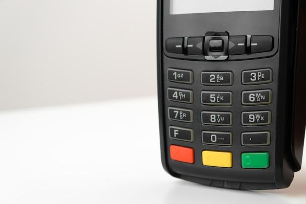 Pos-терминал или устройство для чтения кредитных карт на белом столе с копией пространства