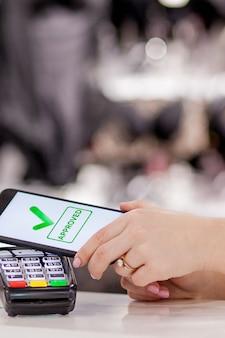 Pos терминал, платежный автомат с мобильным телефоном на фоне магазина. бесконтактный платеж по технологии nfc