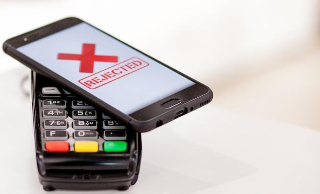 Pos-терминал, платежный автомат с мобильным телефоном на фоне магазина. бесконтактная оплата по технологии nfc.