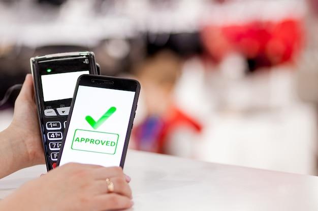Pos-терминал, платежный автомат с мобильным телефоном в магазине