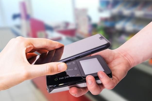 Pos端末とスマートフォン。背景にはスーパーマーケットのチェックアウトがあります。銀行設備。取得。銀行のクレジットカードの受け入れ。非接触型決済。