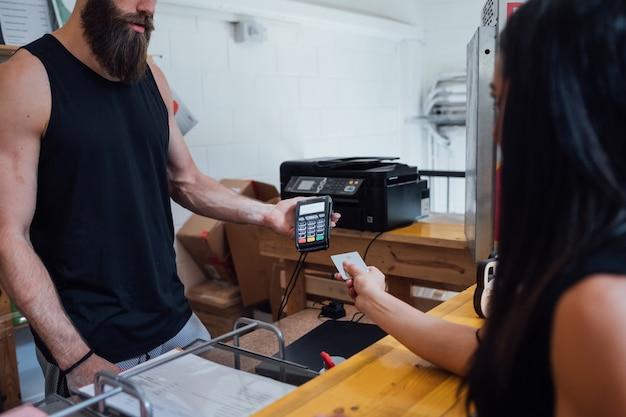 Женщина-клиент расплачивается кредитной картой с помощью pos-терминала