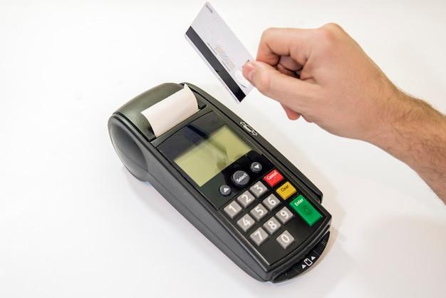 男性の手は、カードマシンのピンパッドまたはピン端子にピンコードをダイヤルし、白い背景に白いクレジットカードが挿入された状態で挿入します。クレジットカードでの支払い -  pos端末を持っているビジネスマン。