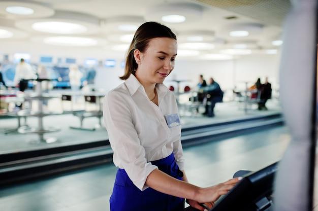 カフェでposターミナルまたはキャッシュボックスで働くウェイターの女の子。人とサービスのコンセプト