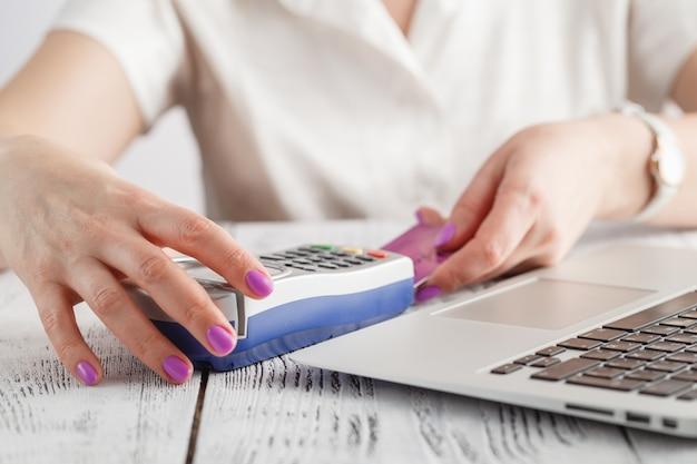 女性の手が白いクレジットカードをクレジットカードマシン(pos端末)に挿入します。
