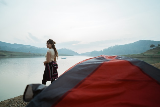 Pose caucasian woman standing near a tent