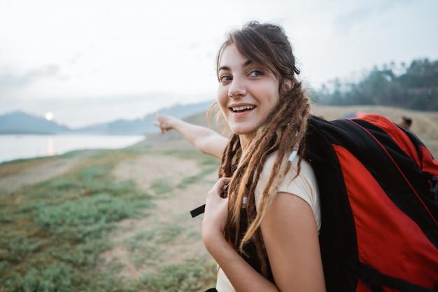 Поза кавказской женщины с рюкзаком, оглядываясь назад