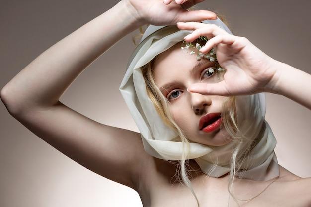 雑誌のポーズ。頭に白いスカーフを付けた雑誌の表紙の素敵なポーズを示すプロの青い目のモデル