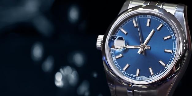 Наручные часы posh, размещенные на блестящем стеклянном полу