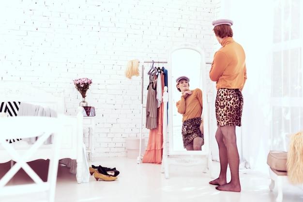집에서 포즈. 패션 조각으로 가득 찬 그의 방에 머물고 더 나은 변형을 선택하는 매력적인 젊은 남자