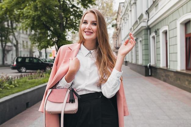 Позирует привлекательной стильной улыбающейся женщины, идущей по городской улице в розовом пальто весенней модной тенденции, элегантного стиля