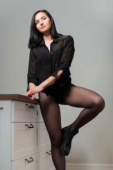 Posing beautiful young woman in black nylon tights and stylish leather boots