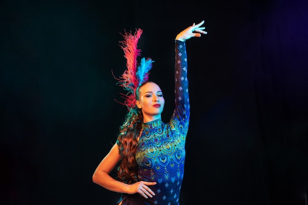 ポーズ。カーニバルの美しい若い女性、ネオンの光の中で黒い壁に羽を持つスタイリッシュな仮面舞踏会の衣装。広告のコピースペース。休日のお祝い、ダンス、ファッション。お祝いの時間、パーティー。