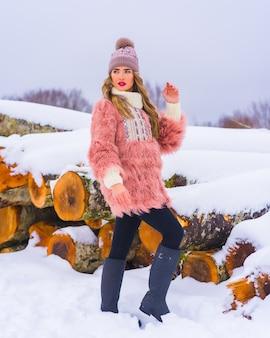 눈에 분홍색 모피 재킷과 보라색 모자와 금발 모델 포즈. 얼음으로 자른 나무 옆, 겨울 생활