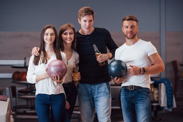 In posa per la telecamera. i giovani amici allegri si divertono al bowling durante i fine settimana