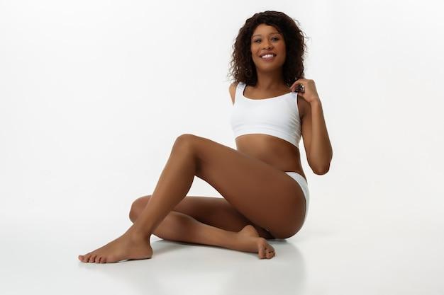 자신감을 가지고 자신을 사랑하십시오. 슬림 그을린 여자의 흰 벽에. 잘 관리 된 모양과 피부를 가진 아프리카 계 미국인 모델. 미용, 자기 관리, 피트니스, 슬리밍 개념. 보건 의료.