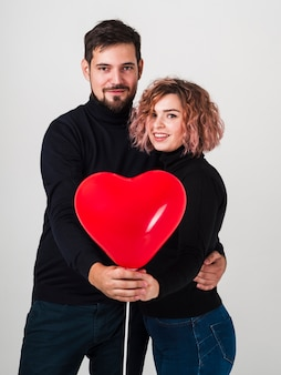 Posing couple with balloon for valentines