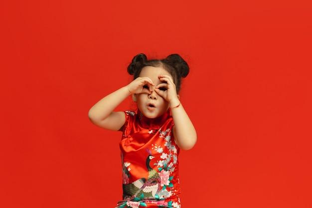 Posa carina, in cerca di regali. . bambina sveglia asiatica isolata sulla parete rossa in vestiti tradizionali. celebrazione, emozioni umane, concetto di vacanze. copyspace.