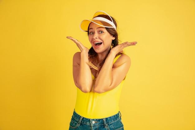 Позирует мило, улыбается. портрет кавказской женщины на желтом фоне студии. красивая женская модель в кепке. понятие человеческих эмоций, выражения лица, продаж, рекламы. лето, путешествия, курорт.