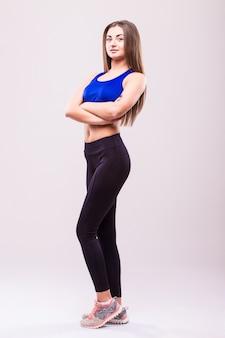 Позирует фитнес сексуальная женщина, изолированные на белом фоне