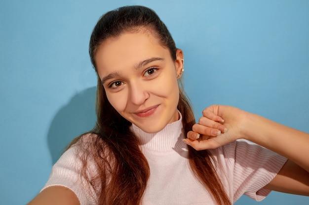 Позирует для селфи. портрет кавказской девочки-подростка на синем фоне. красивая модель в повседневной одежде. понятие человеческих эмоций, выражения лица, продаж, рекламы. copyspace. выглядит счастливым.