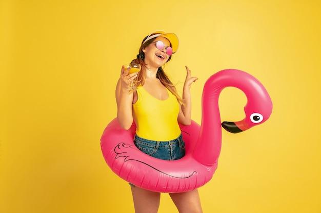 칵테일과 함께 해변 반지에 포즈. 노란색 바탕에 백인 여자의 초상화입니다. 모자에 아름 다운 여성 모델입니다. 인간의 감정, 표정, 판매, 광고의 개념. 여름철, 여행, 리조트.