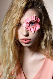 春のポーズ。顔に花と春の問題のポーズをとって優しい若いブロンドの髪の女性