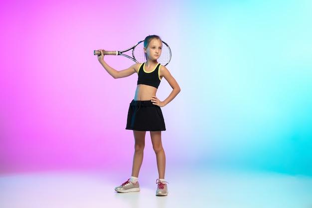 ポーズ。ネオンの光のグラデーションの背景に分離された黒いスポーツウェアの小さなテニスの女の子。白人モデル、運動と行動のスポーツキッズトレーニング。スポーツ、運動、子供の頃のコンセプト。