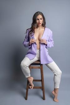 모델 포즈. 스튜디오에서 맨발로 포즈를 취하는 흰색 꽉 바지에 클럽 블레이저에 아름다운 섹시한 메이크업 여자