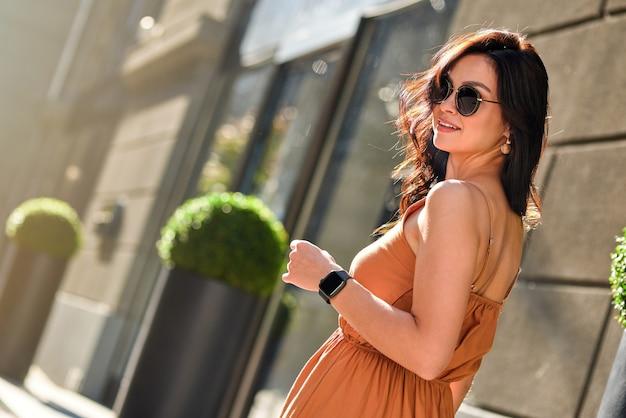 야외에서 포즈. 여름 드레스와 안경을 쓰고 카메라를 보고 화창한 날 도시 거리를 걷는 동안 웃고 있는 젊은 행복한 백인 여성의 초상화. 사람들의 라이프 스타일과 패션