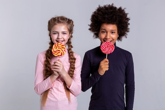 Posing for photoshoot. positive beaming pretty friends participating in photo project while biting hard candies