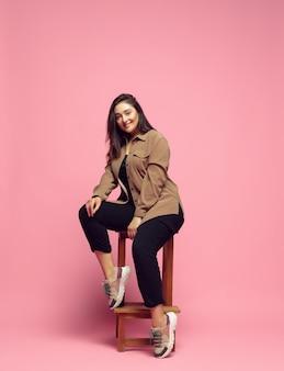 Позирует стильную элегантность молодая женщина в повседневной одежде на розовом фоне бодипозитивный персонаж