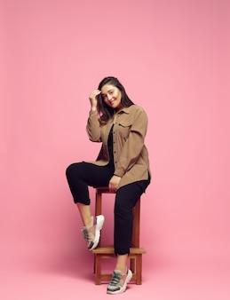 분홍색 배경에 캐주얼웨어를 입은 세련된 우아함 젊은 여성이 포즈를 취하고 있습니다.