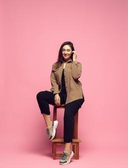 분홍색 배경에 캐주얼웨어를 입은 세련된 우아함 젊은 여성