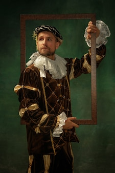 Posing thoughtful. portrait of medieval young man in vintage clothing with wooden frame on dark background. male model as a duke, prince, royal person. concept of comparison of eras, modern, fashion.