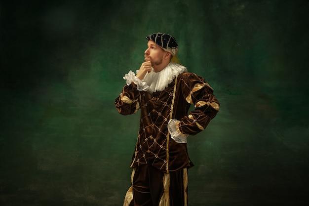 思いやりのあるポーズ。暗い背景の上に立っている古着の中世の若い男の肖像画。公爵、王子、王族としての男性モデル。時代、現代、ファッションの比較の概念。