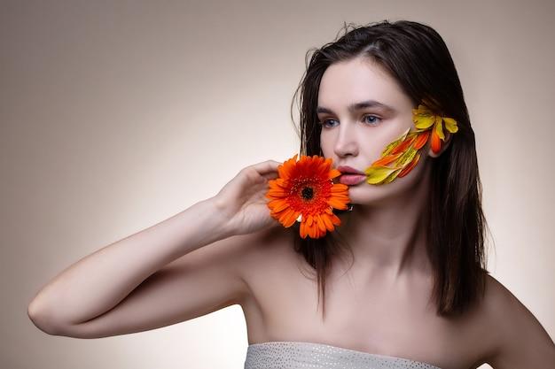 花でポーズ。花でポーズをとるオープンショルダードレスを着ている優しい若い黒髪モデル