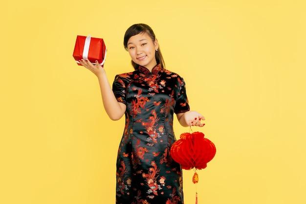 提灯と贈り物でポーズをとって、笑っています。ハッピーチャイニーズニューイヤー2020。黄色の背景にアジアの若い女の子の肖像画。伝統的な服を着た女性モデルは幸せそうに見えます。お祝い、感情。コピースペース。
