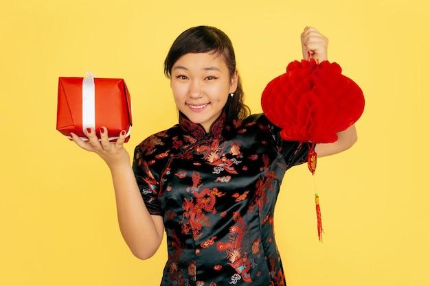 랜턴 및 선물 포즈, 웃고. 행복 한 중국 새 해 2020. 노란색 배경에 아시아 젊은 여자의 초상화. 전통 옷을 입은 여성 모델이 행복해 보입니다. copyspace.