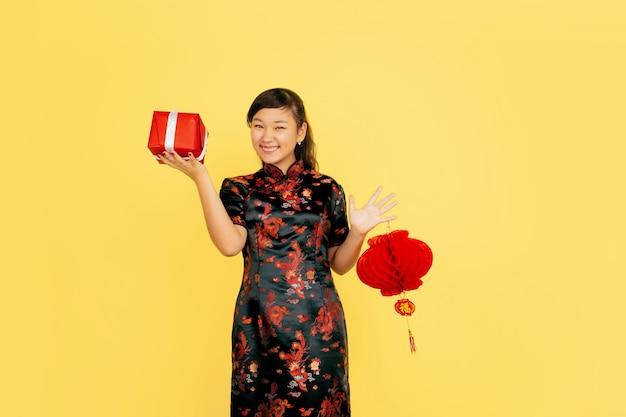 랜턴 및 선물 포즈, 웃고. 해피 중국 설날. 노란색 바탕에 아시아 젊은 여자의 초상화. 전통 옷을 입은 여성 모델이 행복해 보입니다. copyspace.