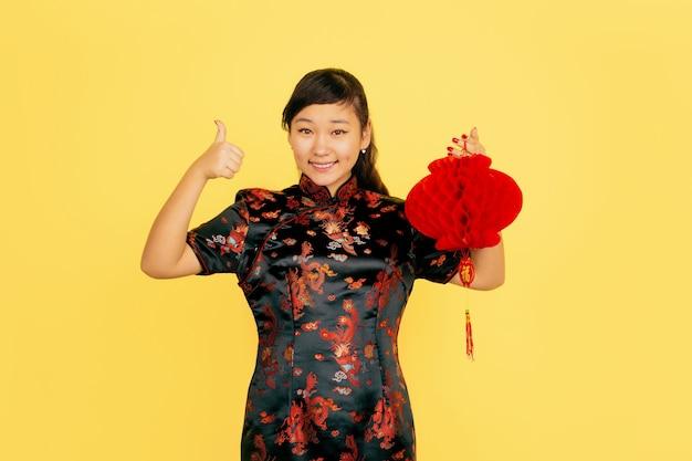 Позирует с фонарем, улыбается, приглашает. счастливого китайского нового года. азиатский портрет молодой девушки на желтом фоне. copyspace.