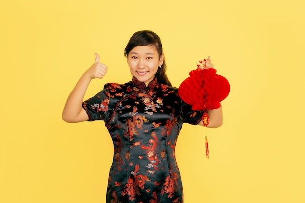 Posing with lantern, smiling, inviting. happy chinese new year. asian young girl portrait on yellow background. copyspace.