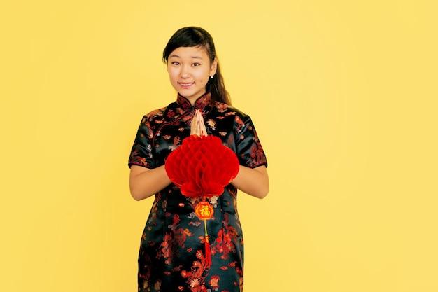 랜턴과 함께 포즈를 취하고 웃으며 감사합니다. 해피 중국 설날. 노란색 바탕에 아시아 젊은 여자의 초상화. 전통 옷을 입은 여성 모델이 행복해 보입니다. copyspace.