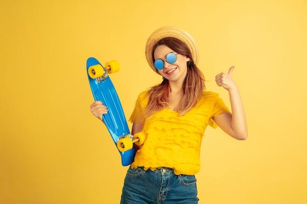 스케이트 보드와 함께 포즈. 노란색 스튜디오 배경에 백인 여자의 초상화입니다.