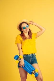 In posa con lo skateboard. ritratto della donna caucasica su sfondo giallo studio.